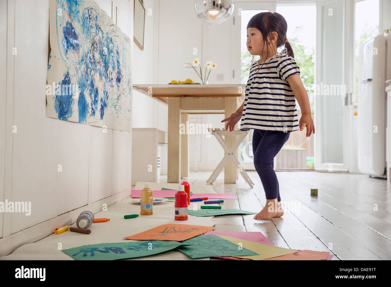 Female toddler inspecting her painting and drawing - Stock Image