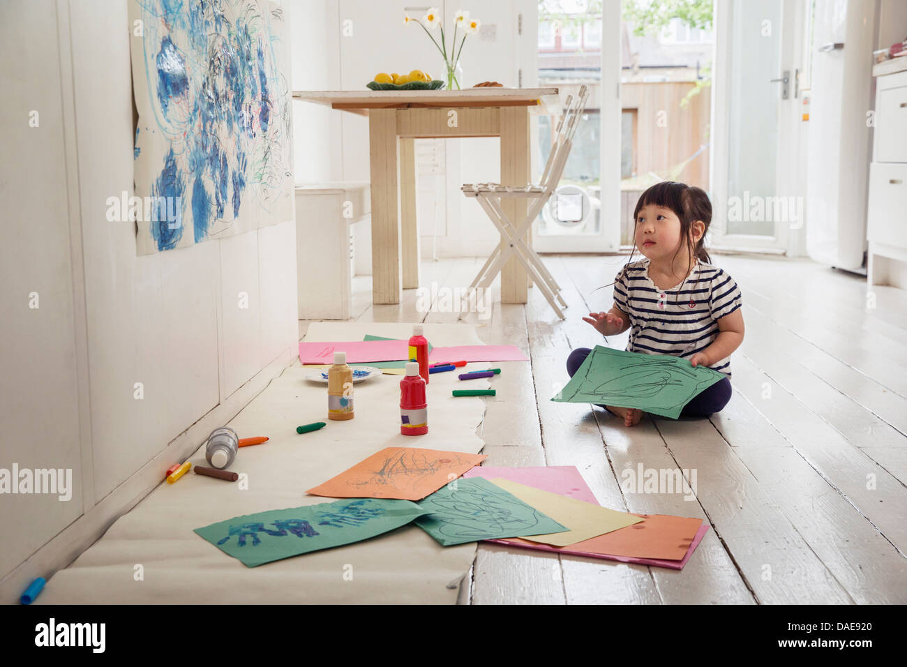 Female toddler sitting on floor with drawings - Stock Image