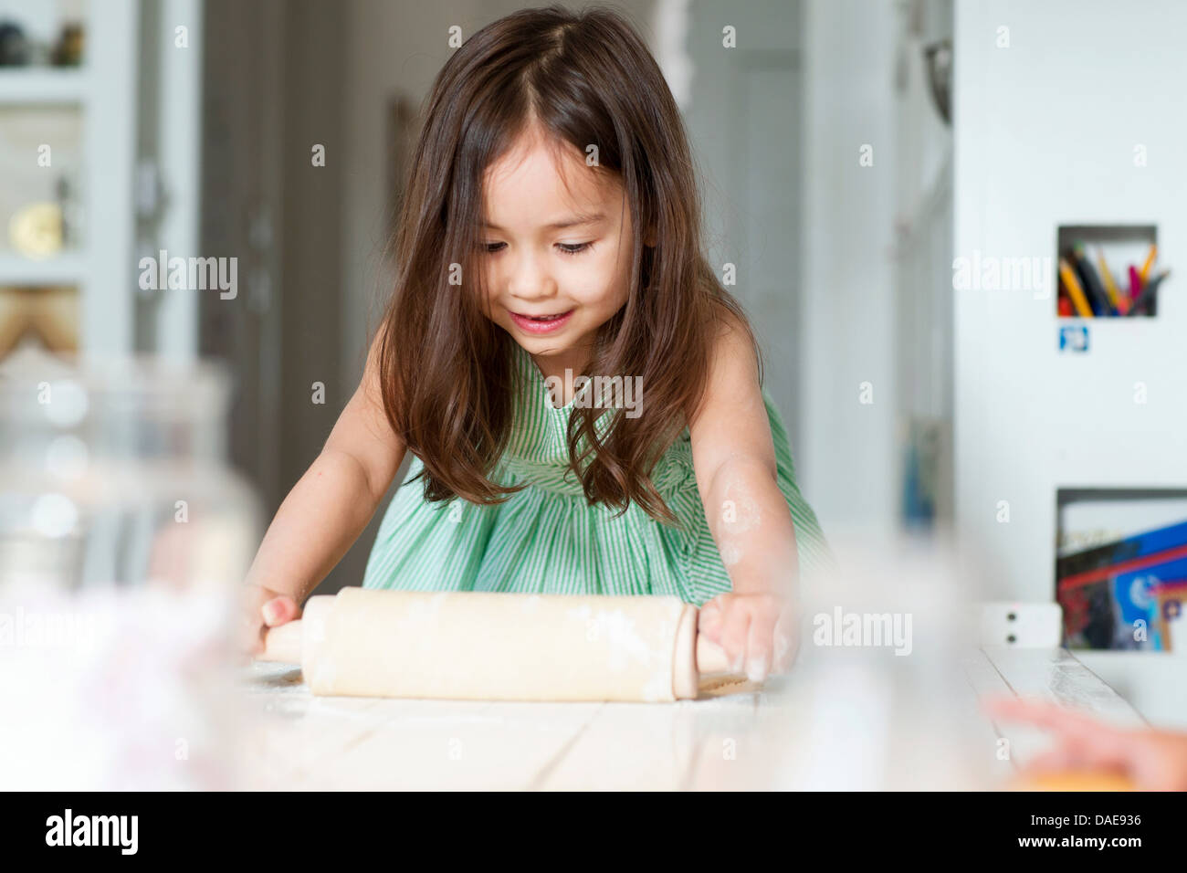 Young girl rolling out pastry on kitchen counter - Stock Image