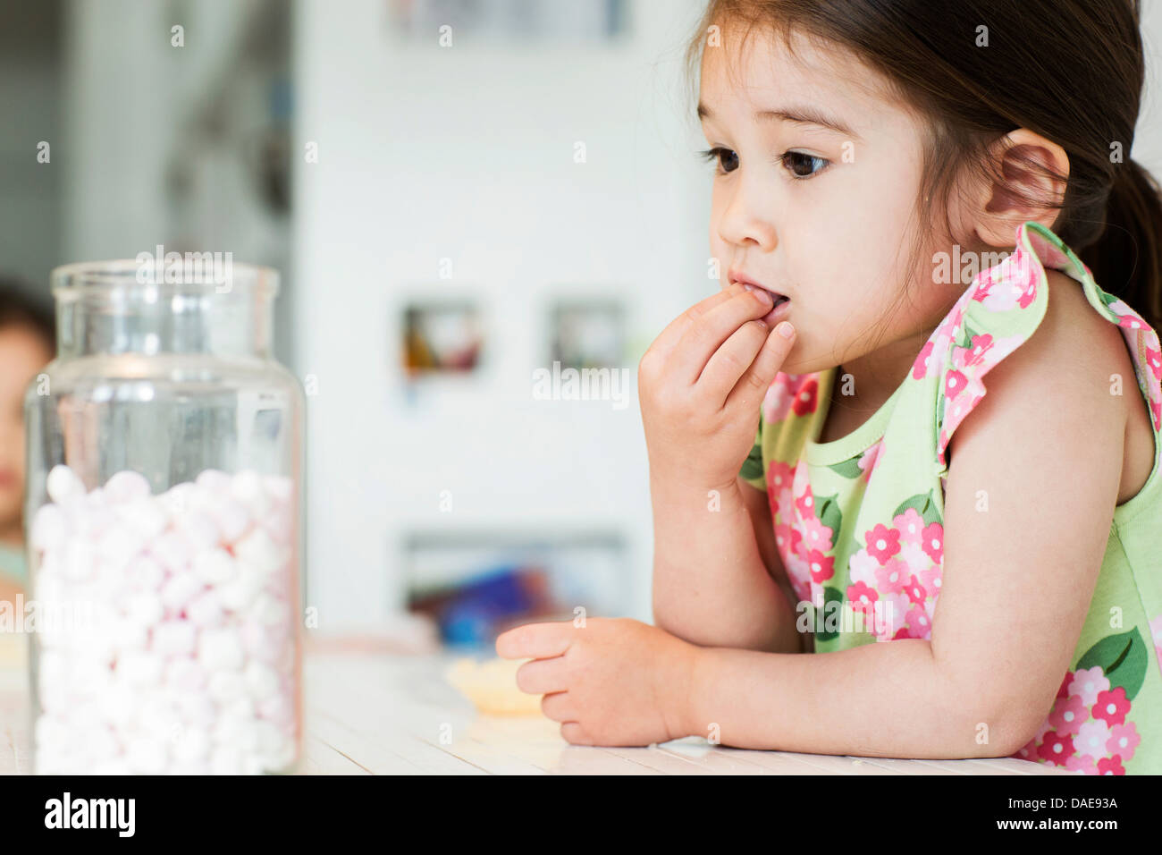 Close up of young girl tasting marshmallows - Stock Image