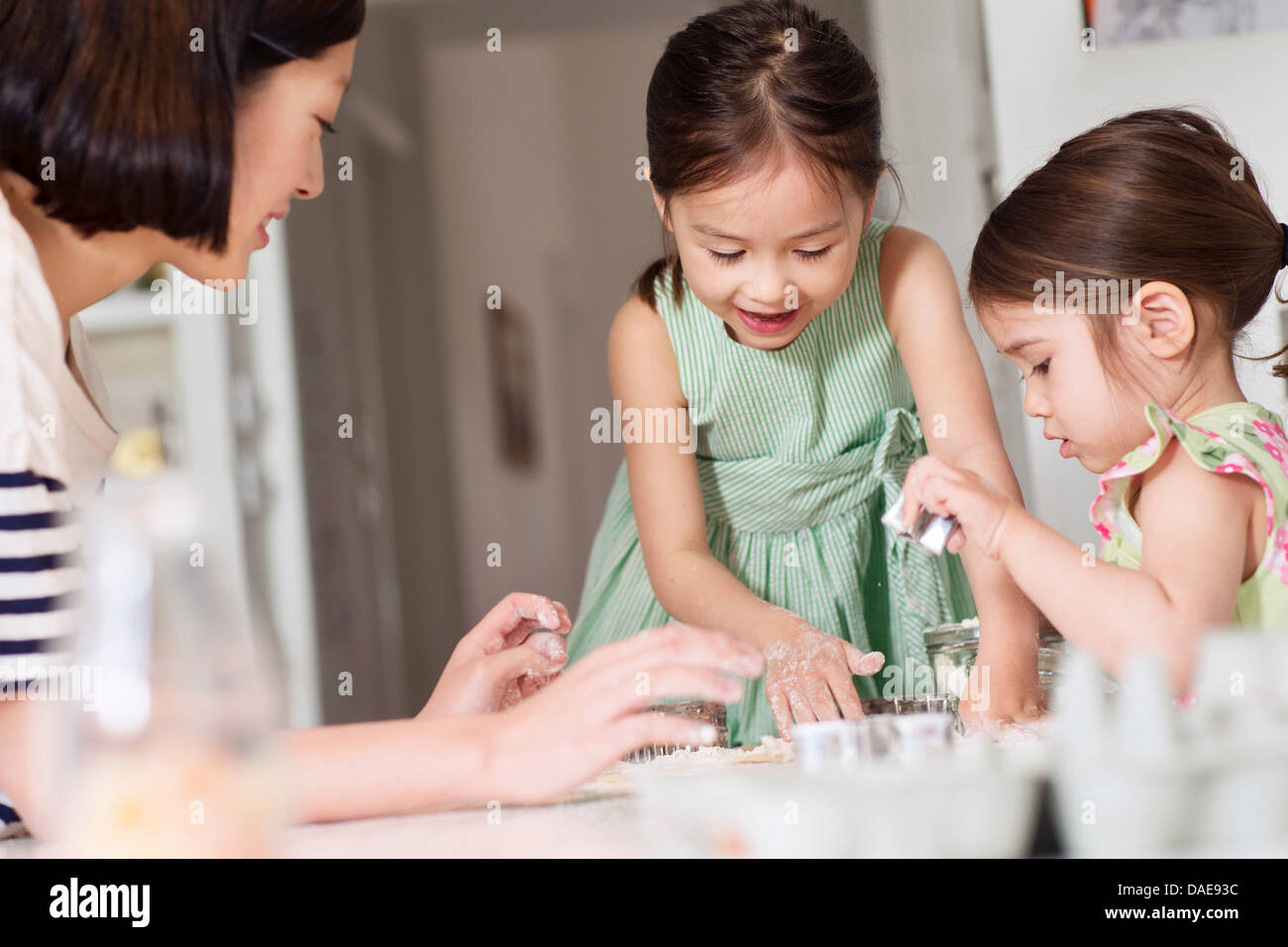 Mother and young daughters making pastry - Stock Image