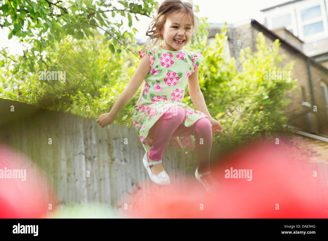Young girl jumping mid air in garden - Stock Image