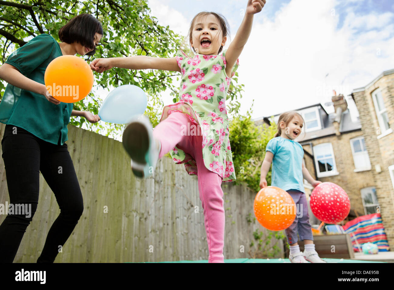Mother and daughters playing in garden with balloons - Stock Image