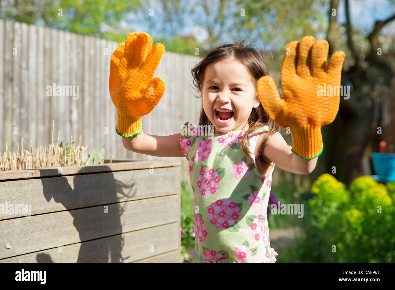 Young girl in garden wearing oversized gloves - Stock Image
