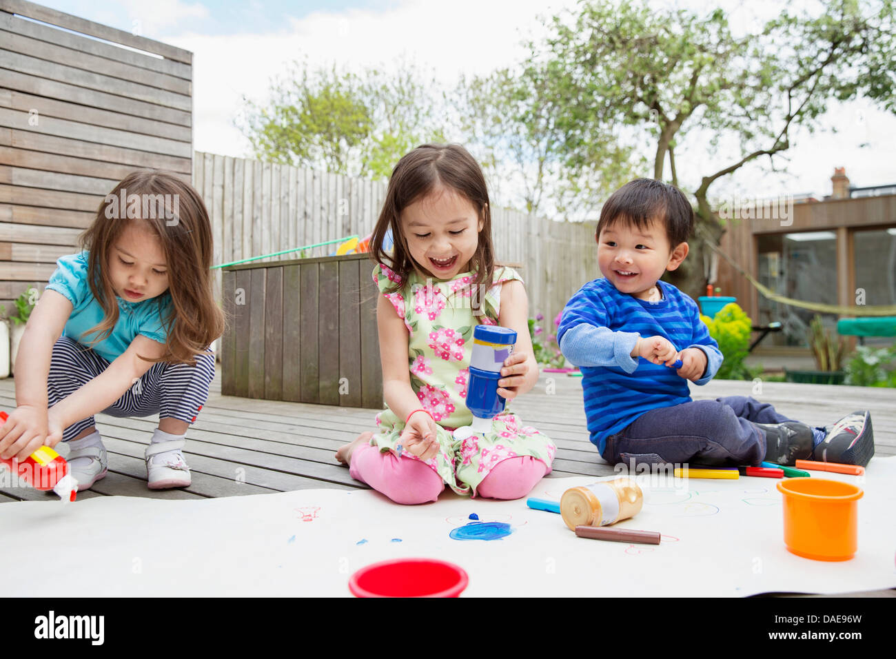 Three young children painting and drawing in garden - Stock Image