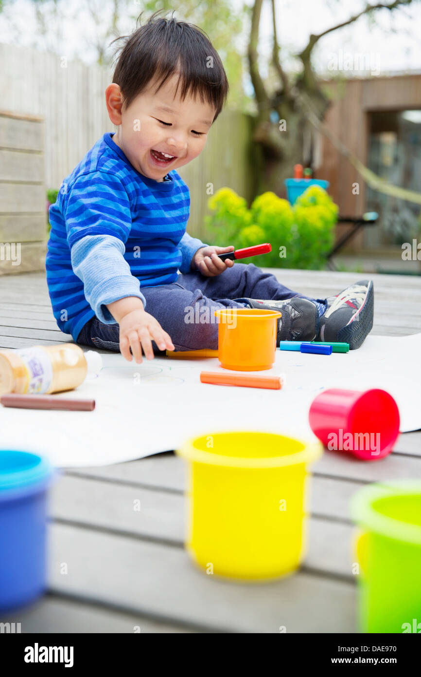 Male toddler drawing in garden - Stock Image