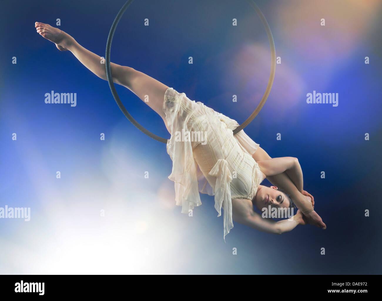 Studio shot of aerialist performing on hoop - Stock Image