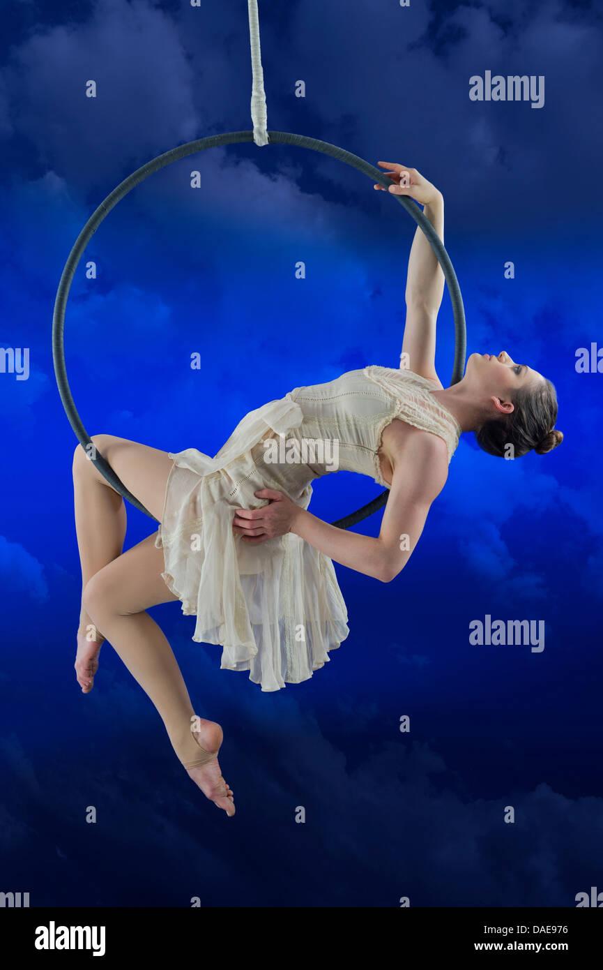 Aerialist performing on hoop against blue background Stock Photo