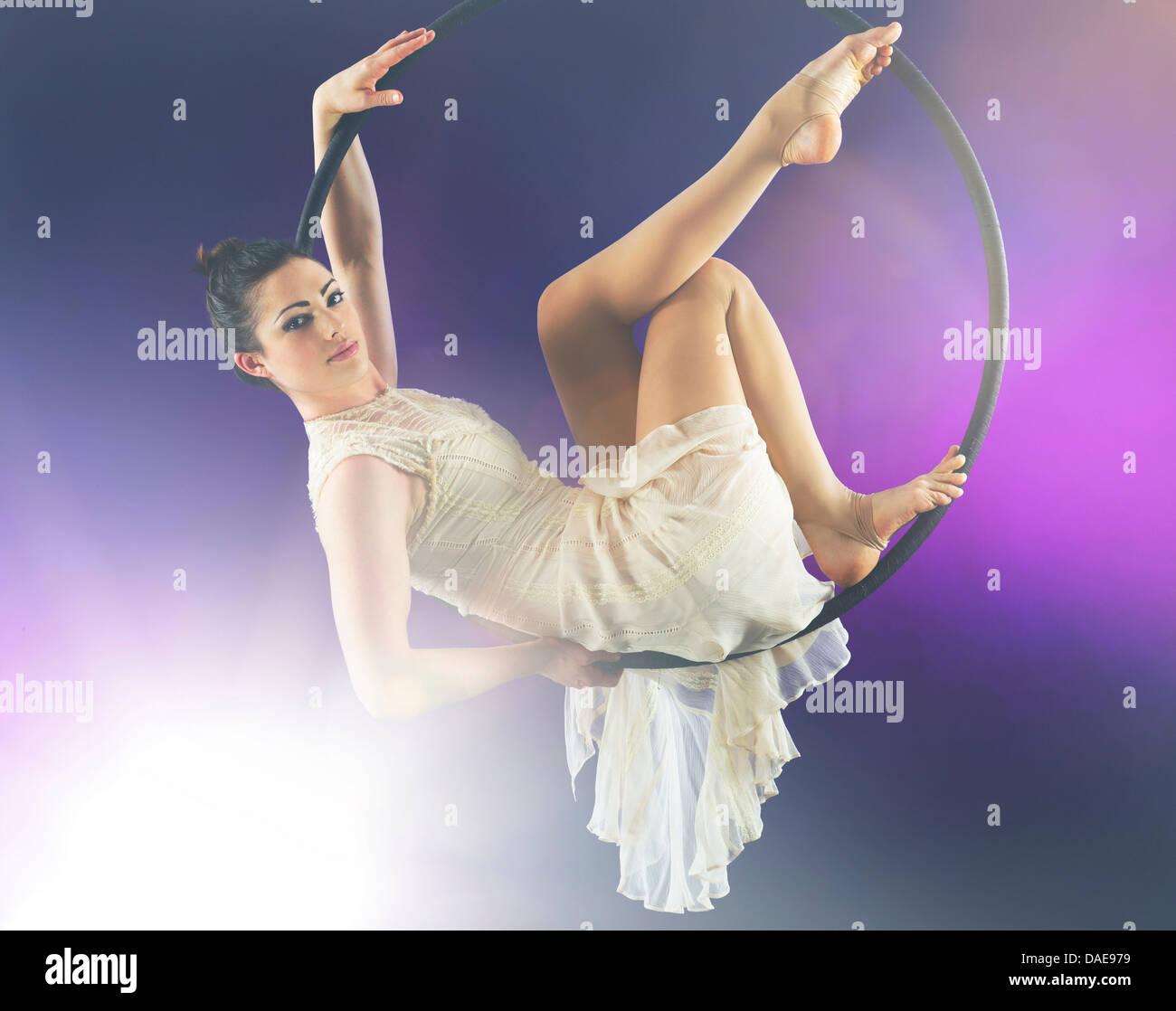 Aerialist poised on hoop against purple background Stock Photo