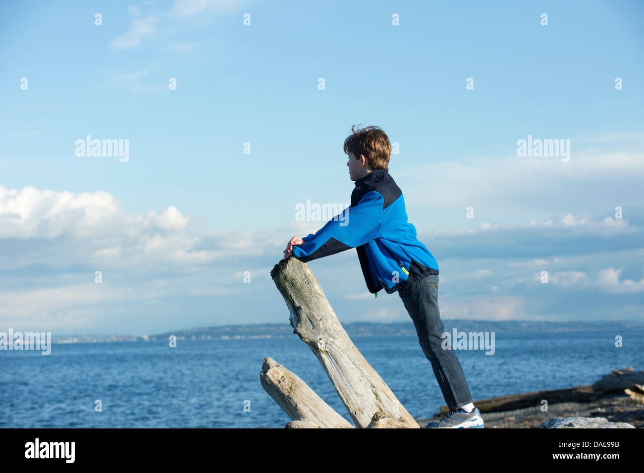 Young boy looking out from Bainbridge Island, Washington State, USA - Stock Image