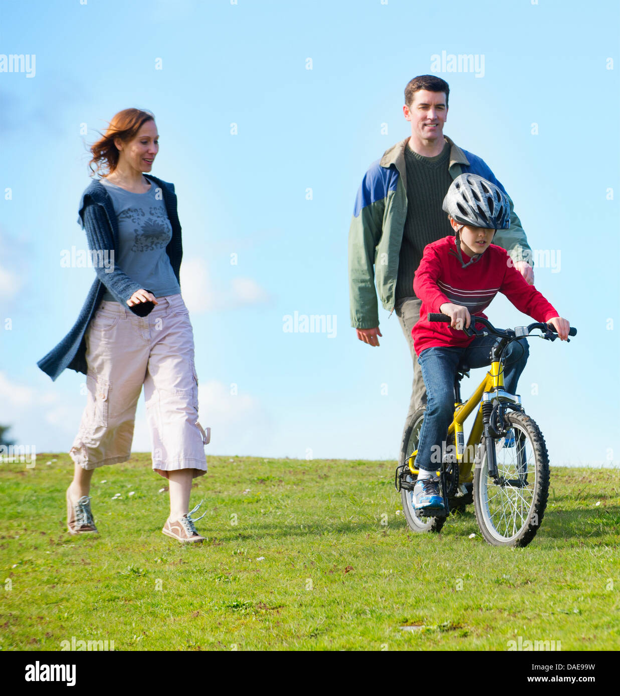 Parents watching son riding bicycle - Stock Image
