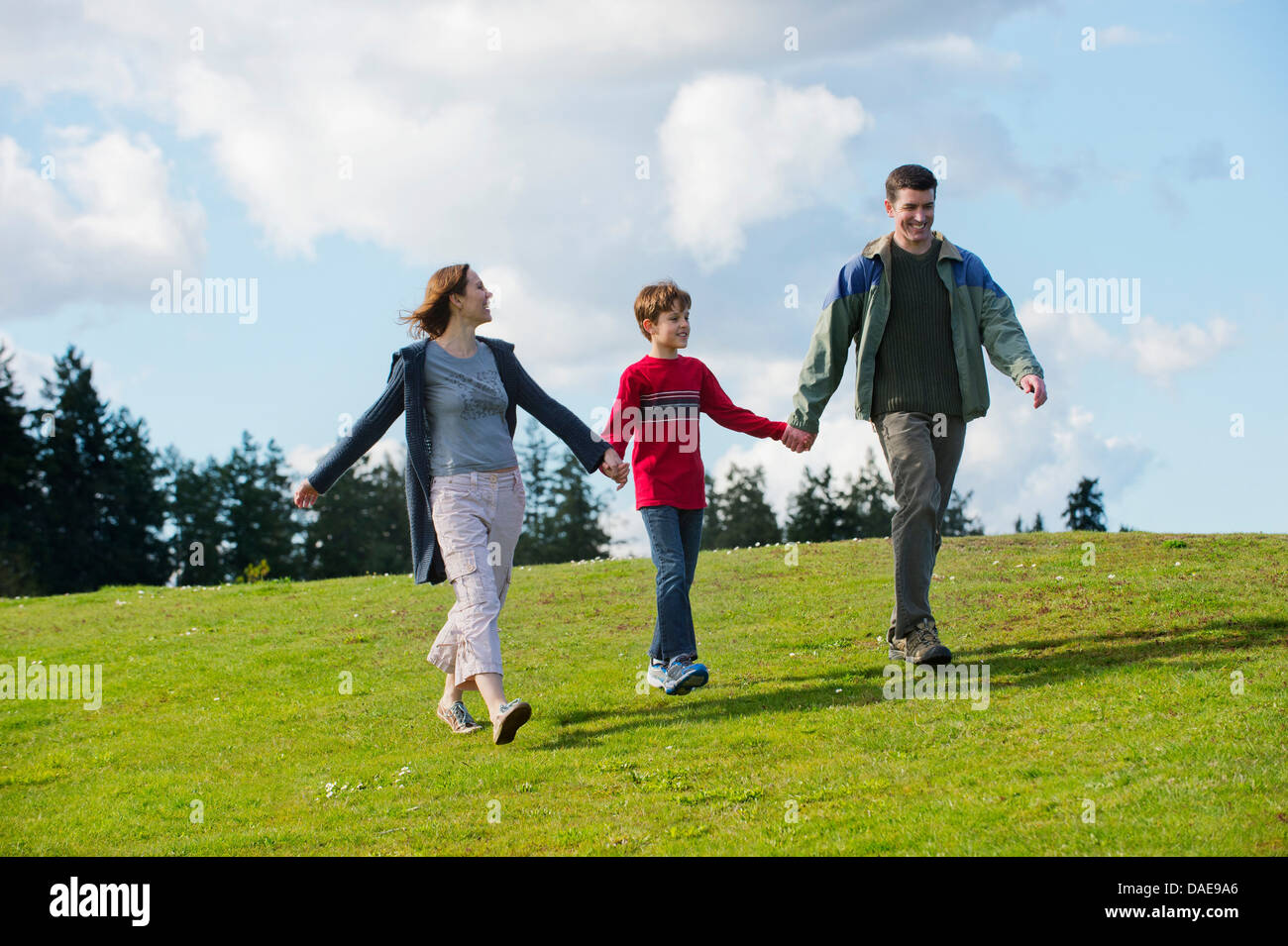 Parents and son walking hand in hand - Stock Image