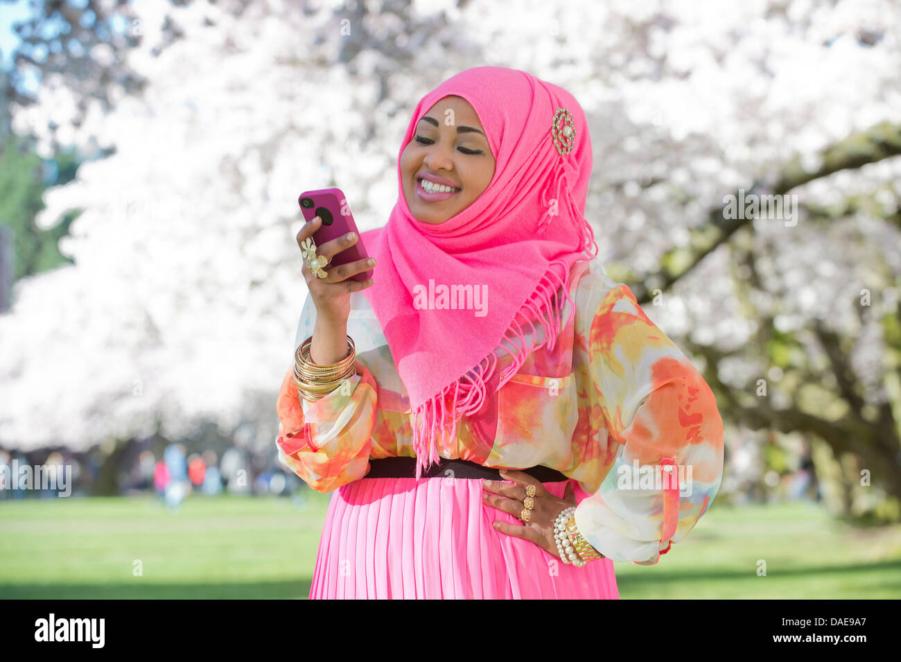 Young woman in park wearing pink headscarf and skirt - Stock Image