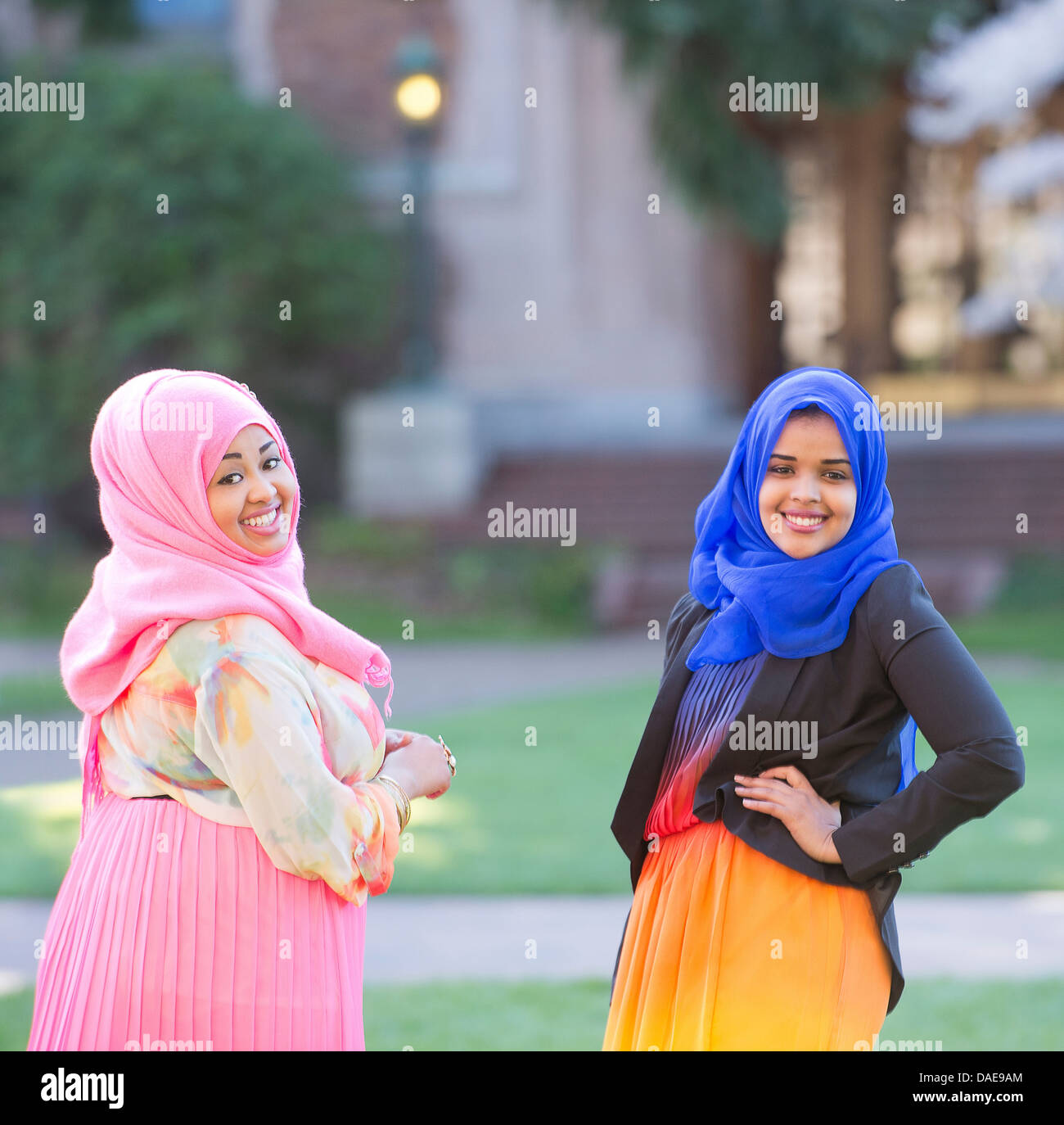 Portrait of two female friends in park wearing colorful headscarves - Stock Image
