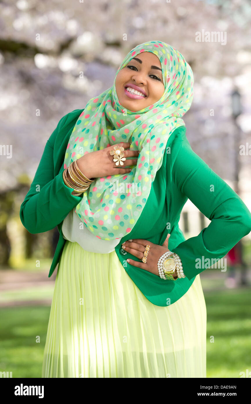 Portrait of young female in park wearing green Stock Photo
