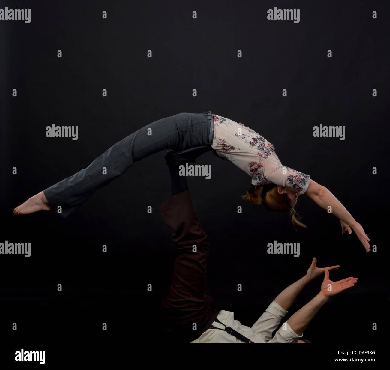 Studio shot of acrobats performing balancing trick - Stock Image