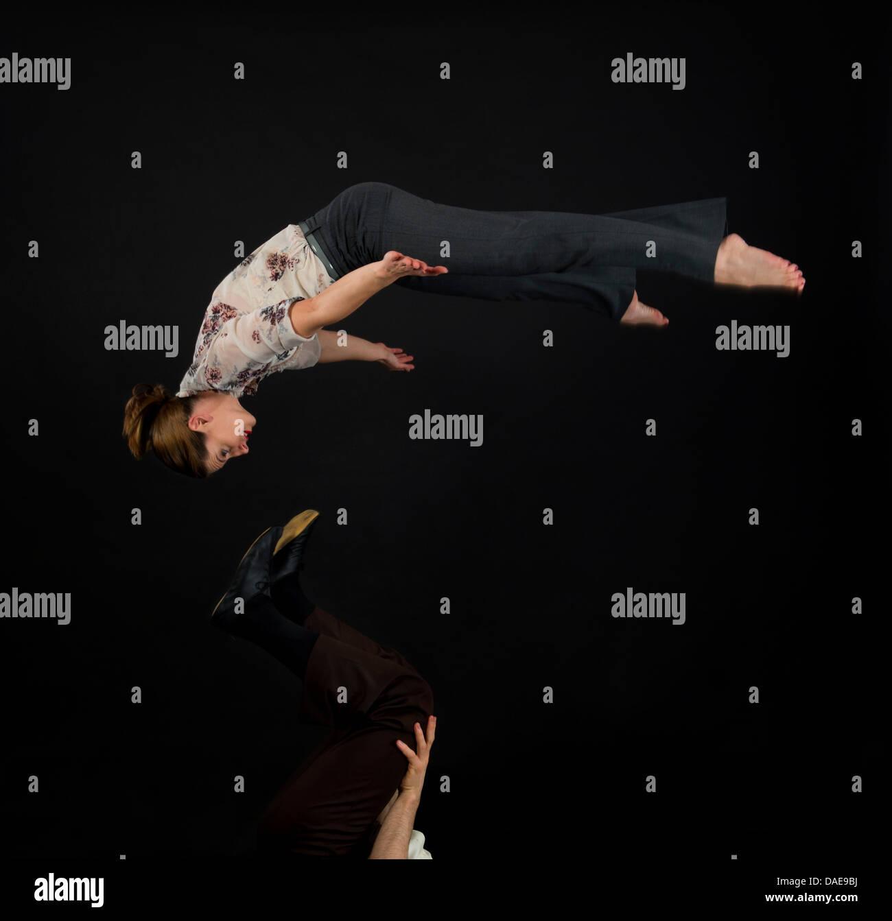 Studio shot of acrobats performing mid air - Stock Image