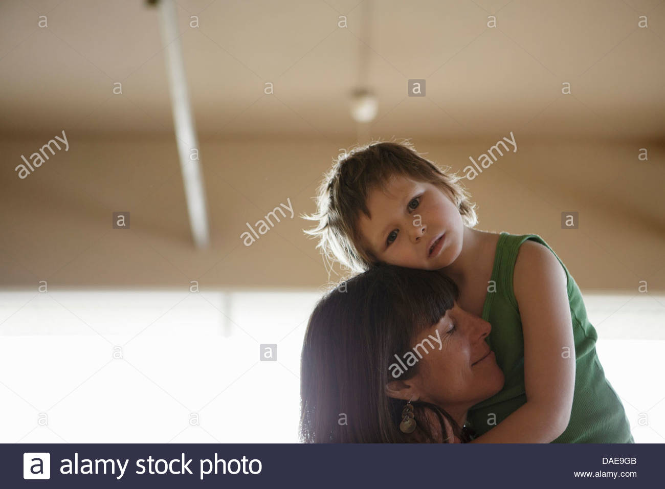 Emotional portrait of mother holding daughter - Stock Image
