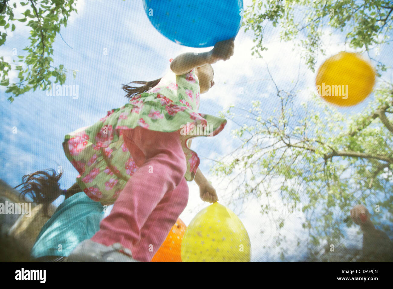 Young girls bouncing on garden trampoline with balloons - Stock Image