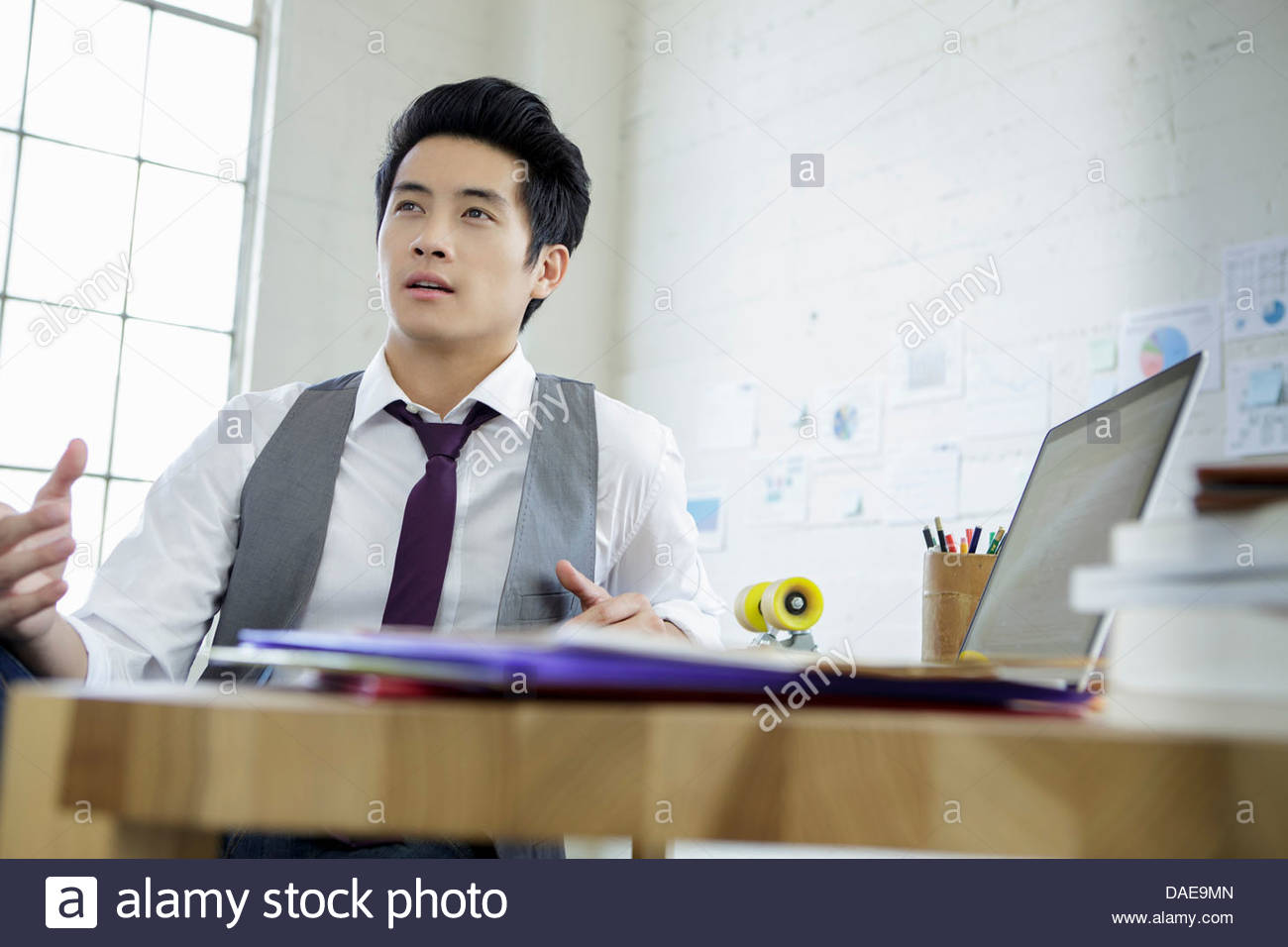 Young man in conversation whilst sitting at office desk - Stock Image