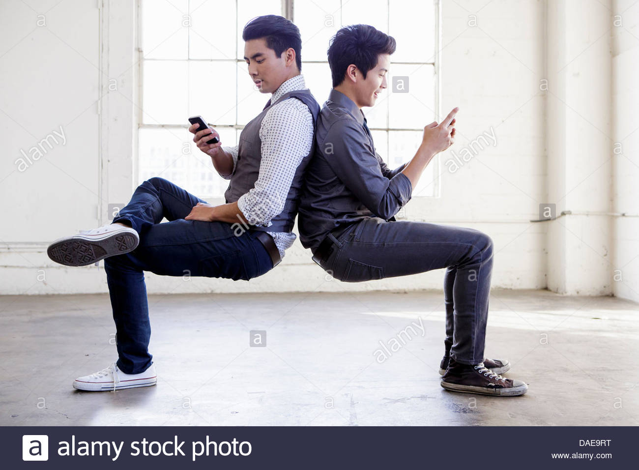 Two young men create back to back void in empty office - Stock Image