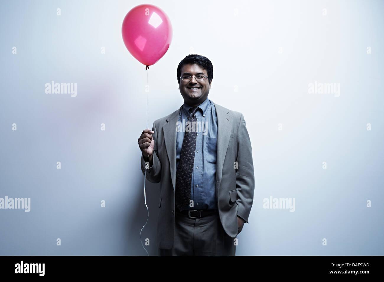 Studio portrait of businessman holding red balloon - Stock Image