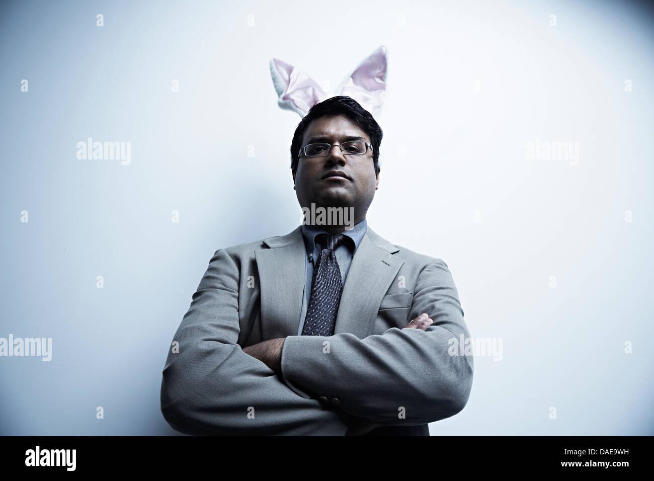 Studio portrait of businessman wearing bunny ears - Stock Image