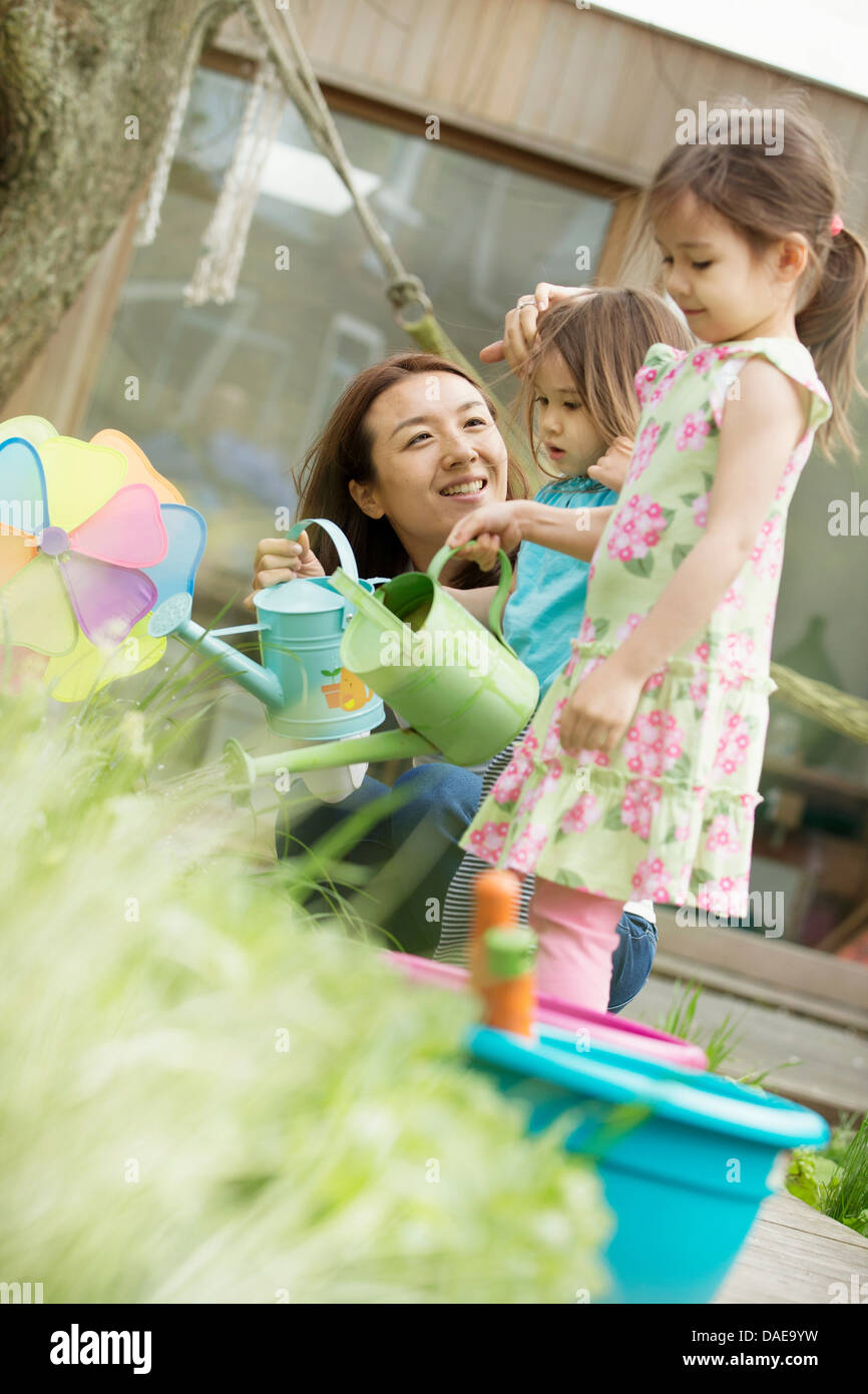 Mother and two daughters with toy watering cans in garden - Stock Image