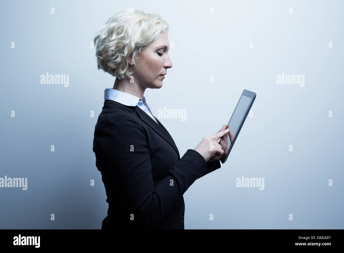 Studio portrait of blond businesswoman looking at digital tablet - Stock Image
