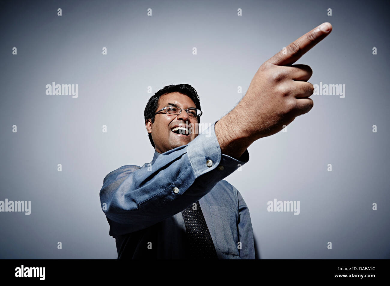 Studio portrait of businessman with exaggerated pointing finger - Stock Image