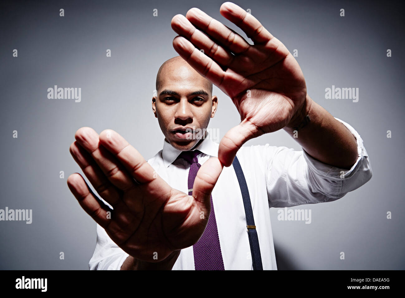 Studio portrait of businessman with exaggerated hands - Stock Image