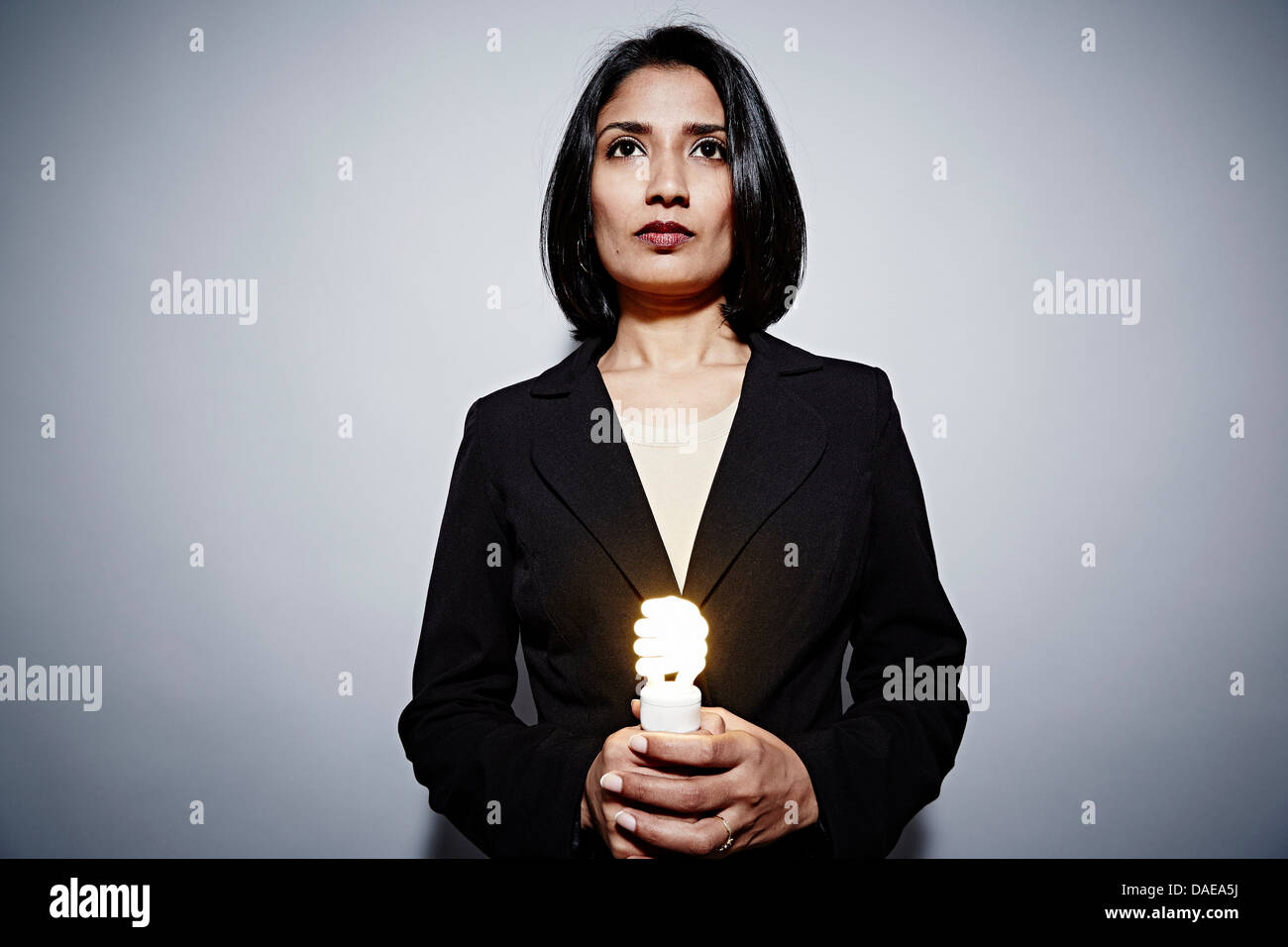 Studio portrait of businesswoman holding energy saving lightbulb - Stock Image