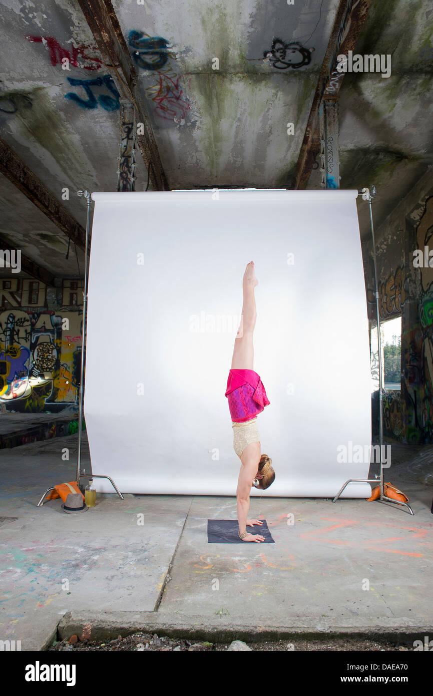 Female acrobat practicing handstand in old industrial interior - Stock Image