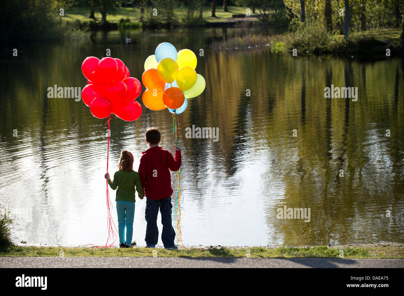 Brother and sister in front of lake with bunches of balloons - Stock Image