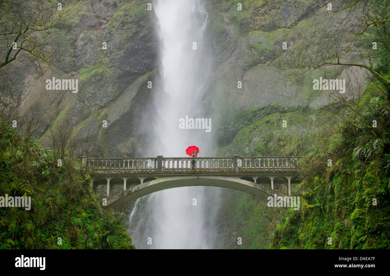 Woman with red umbrella in front of Multnomah Falls, Columbia River Gorge, USA - Stock Image