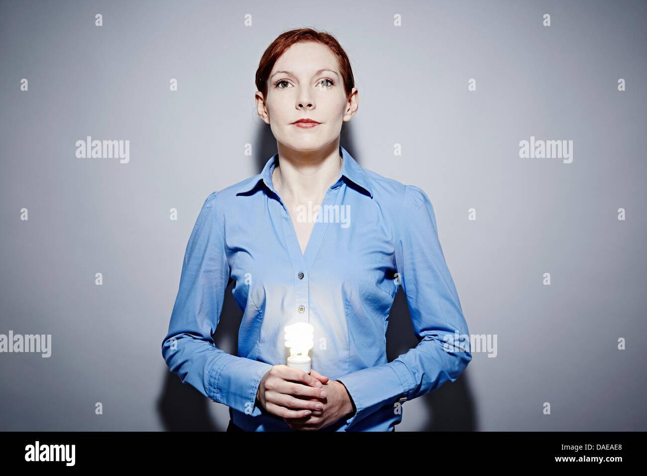 Studio portrait of young business woman holding lit lightbulb - Stock Image