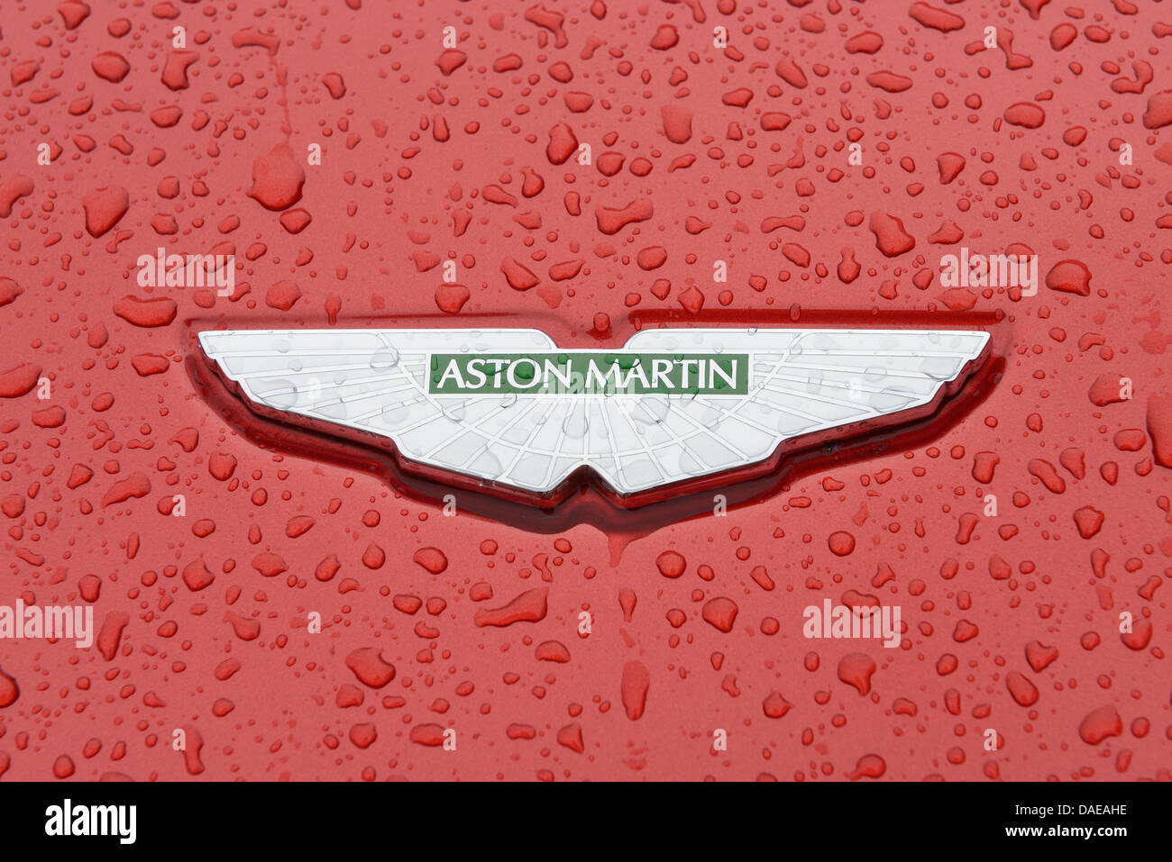 Aston Martin car badge close up on a wet bonnet - Stock Image