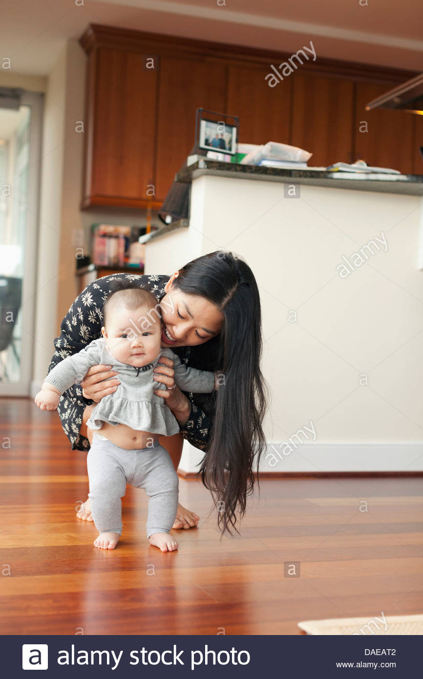 Mother supporting baby girl to walk - Stock Image