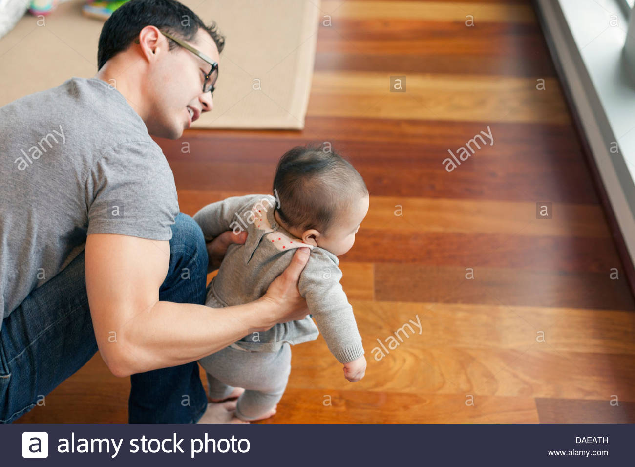 Father supporting baby girl to walk - Stock Image
