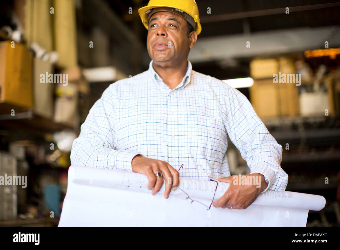 Man in warehouse rolling up blueprint - Stock Image