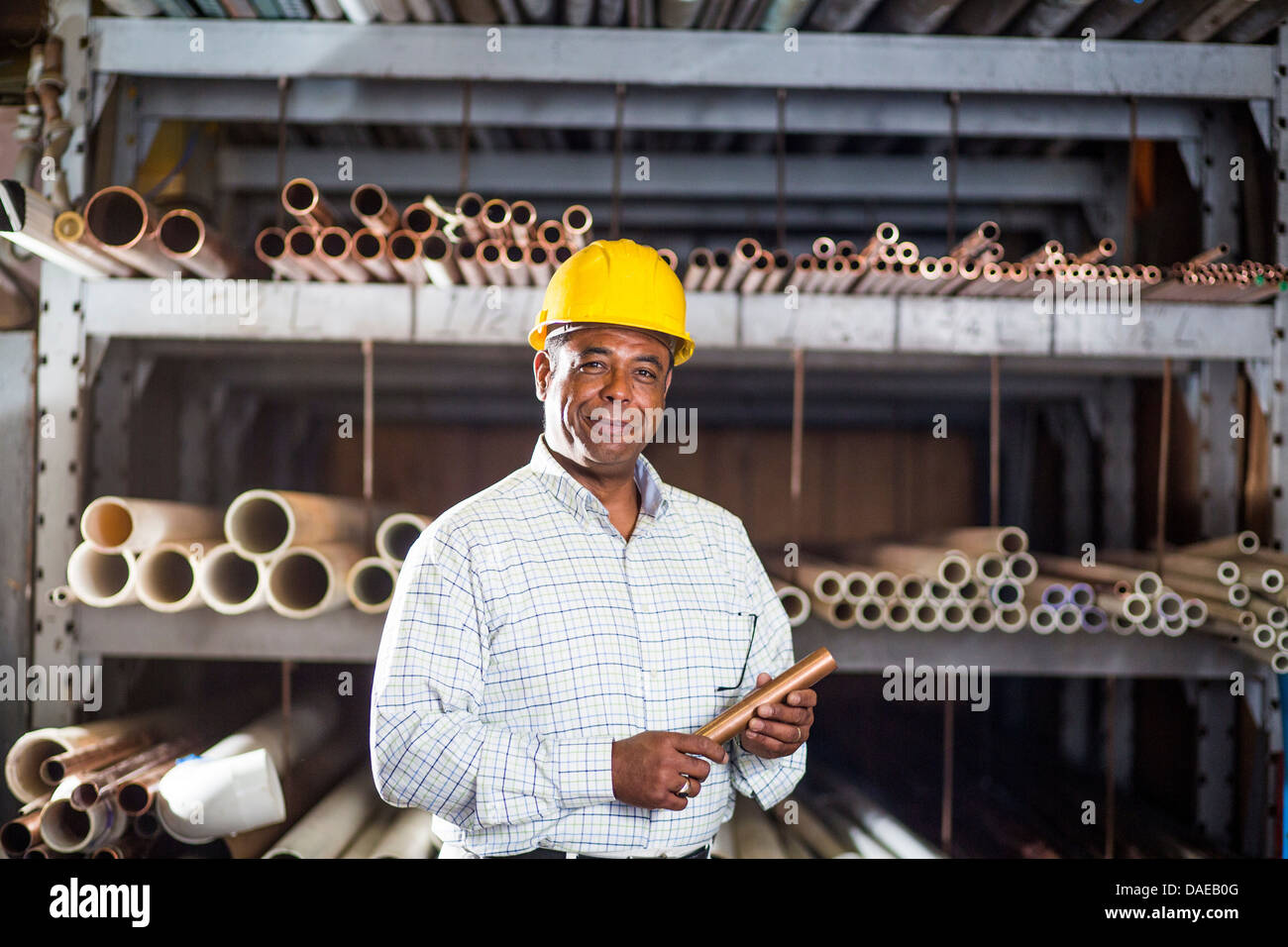 Man in warehouse with copper pipe - Stock Image