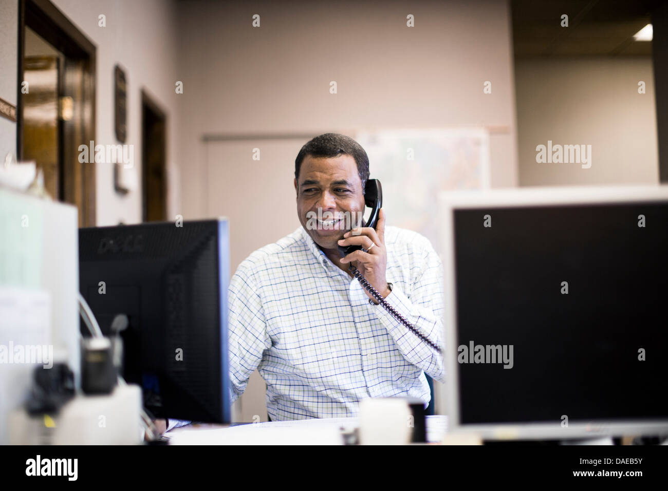 Mature man in office on landline - Stock Image