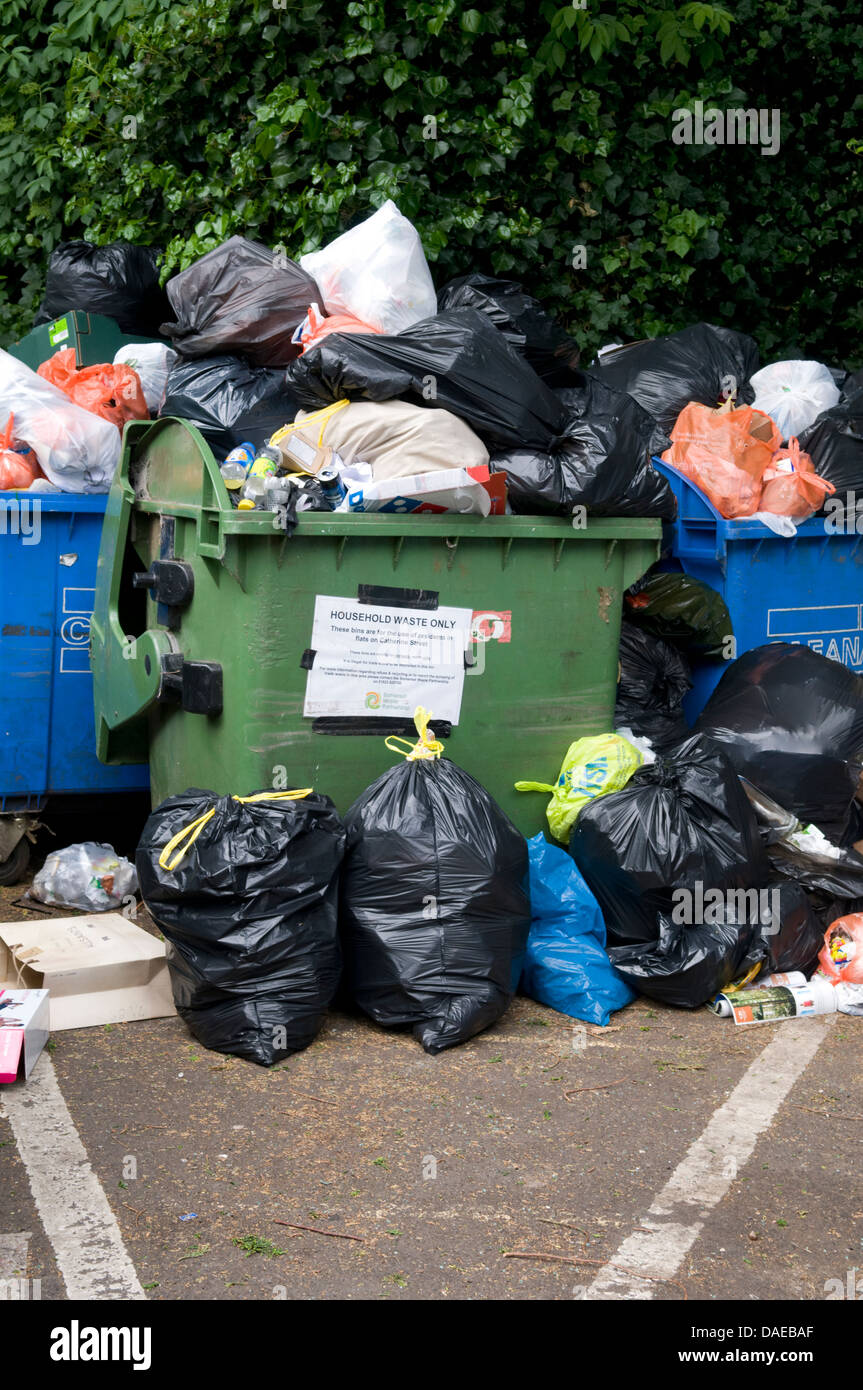 Overflowing refuse collection bins in Frome, Somerset, UK - Stock Image