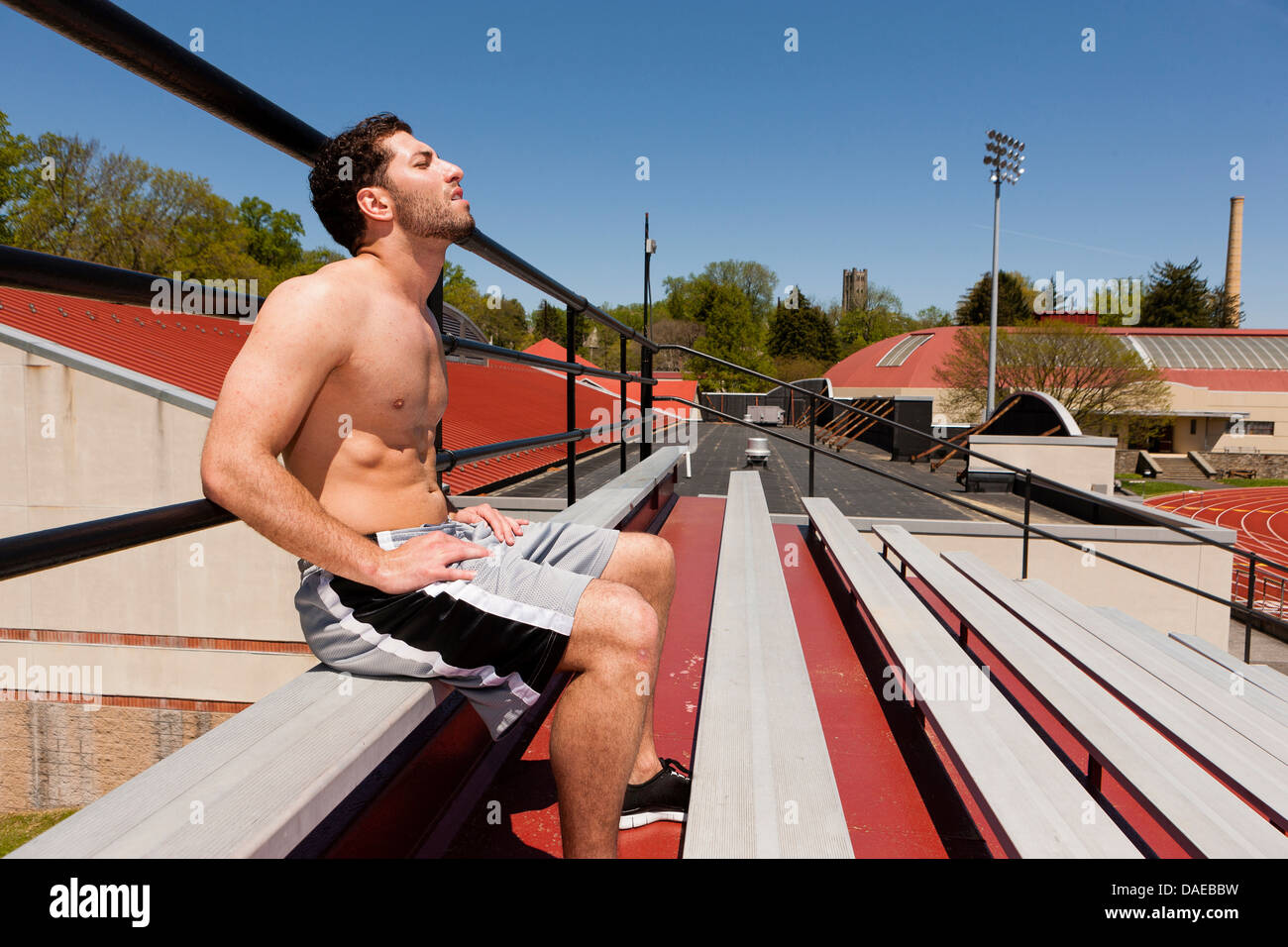 Young athlete taking a break on stadium seats - Stock Image