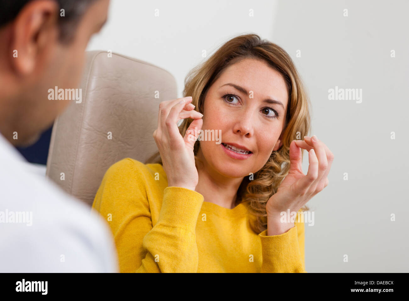 Patient explaining symptom to doctor in hospital - Stock Image
