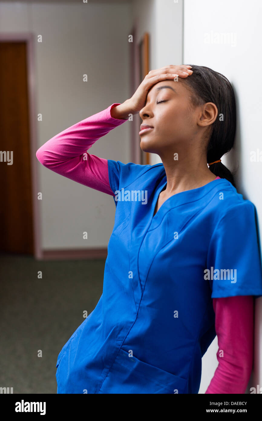 Nurse with eyes closed and hand on head in hospital corridor - Stock Image