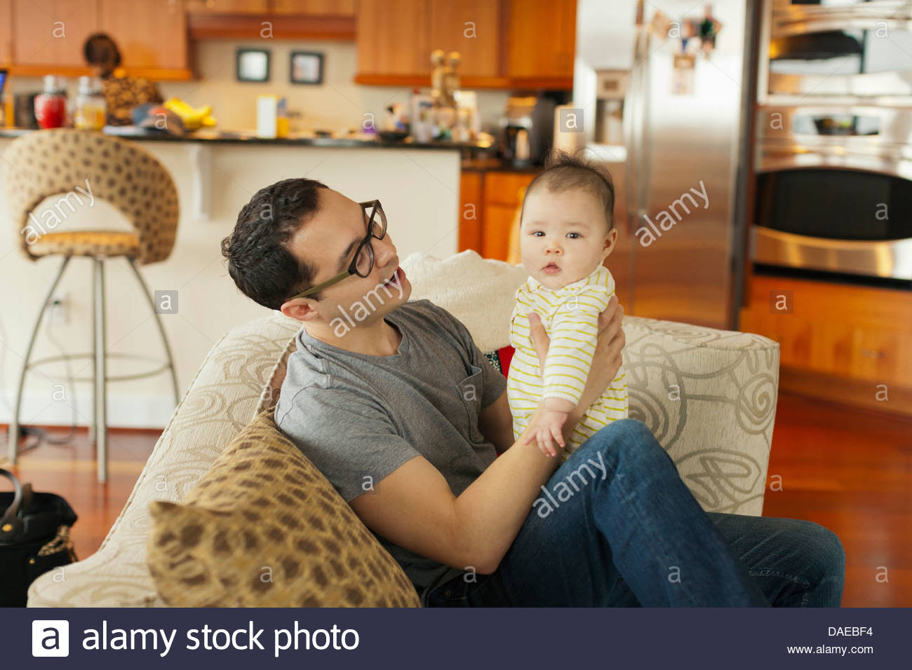 Father sitting on sofa with baby daughter Stock Photo