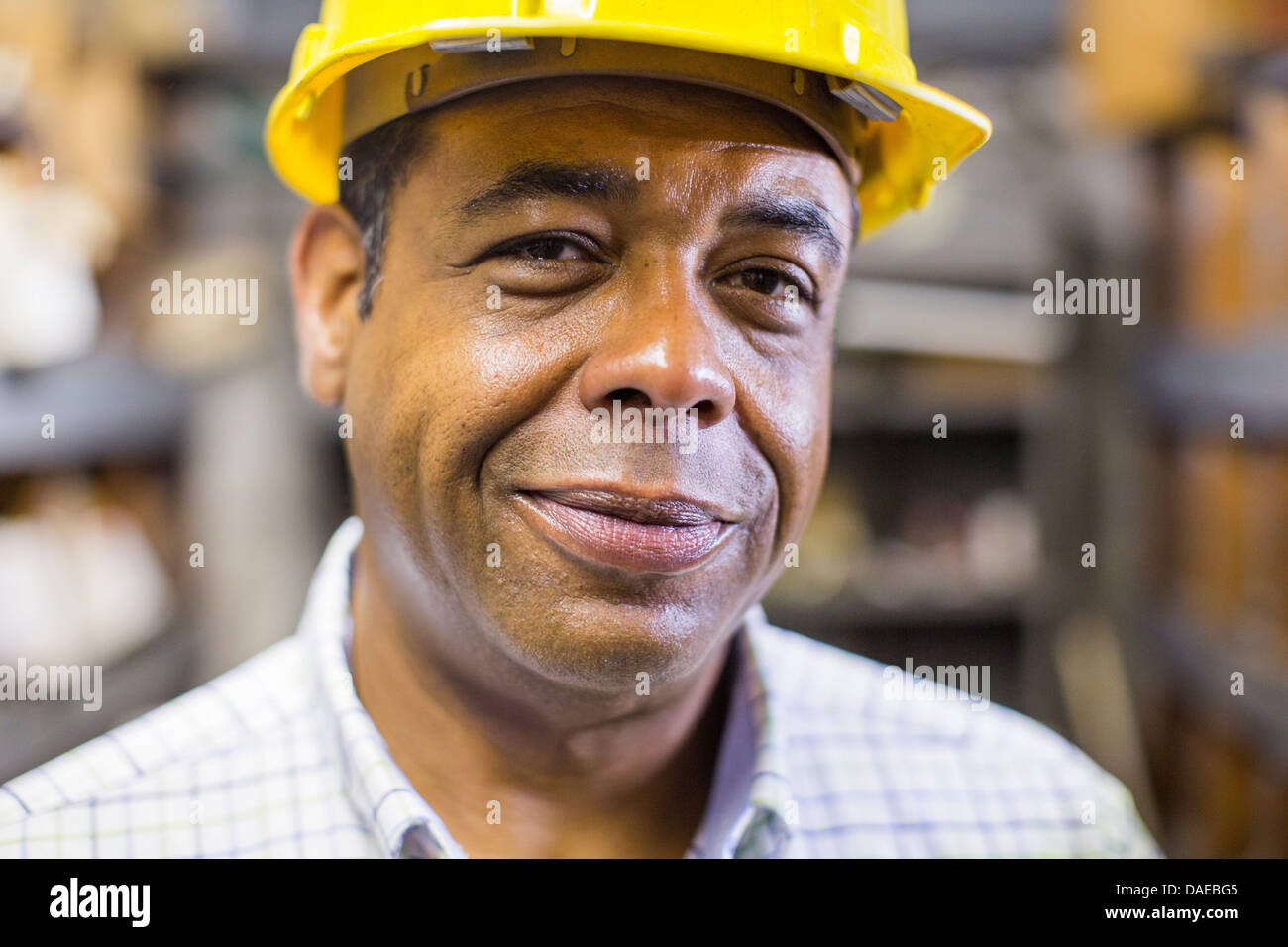 Close up portrait of man in stockroom wearing hard hat - Stock Image