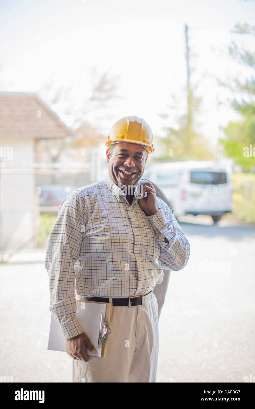 Portrait of man wearing hard hat and carrying clipboard - Stock Image