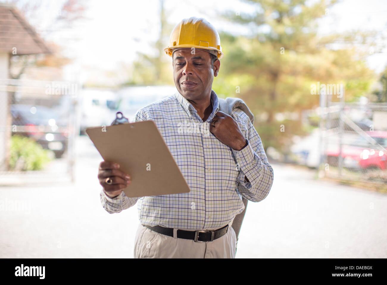 Man wearing hard hat looking at clipboard - Stock Image
